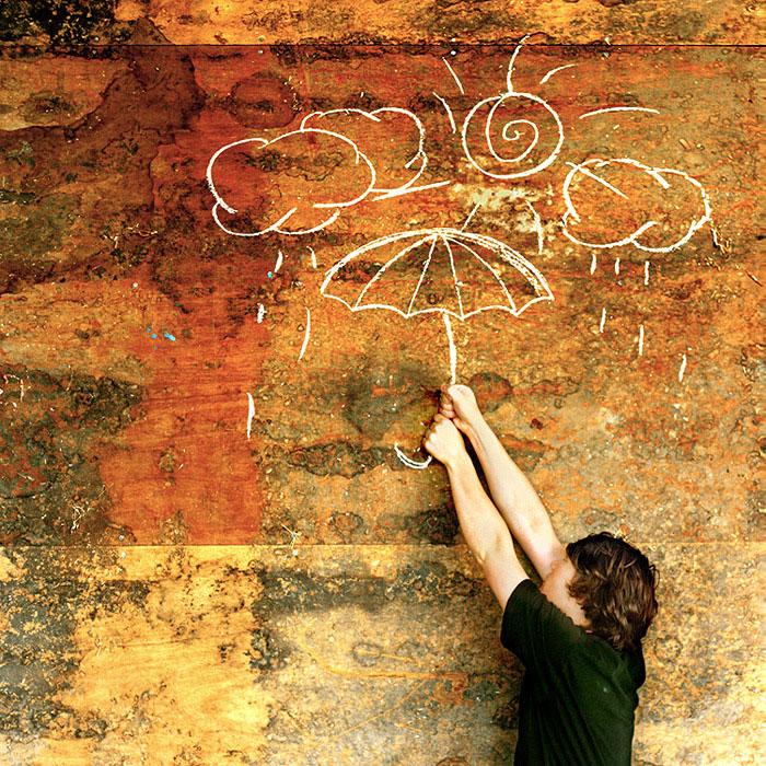 dečak pokušava da uhvati nacrtani kišobran na zidu