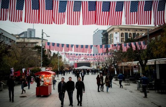 ljudi šetaju ulicom u Prištini koja je ukrašena američkim zastavama
