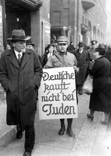 Pripadnik SA u aprilu 1933. sa natpisom kojim se poziva na bojkot jevrejskih radnji u Berlinu