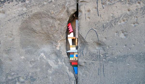 kućica od lego kockica zaglavljena u pukotini zida