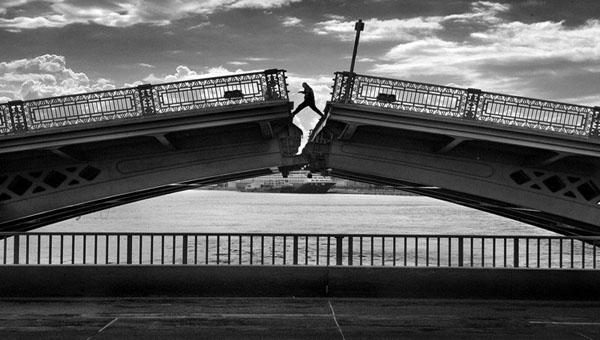 čovek prelazi preko porušenog mosta