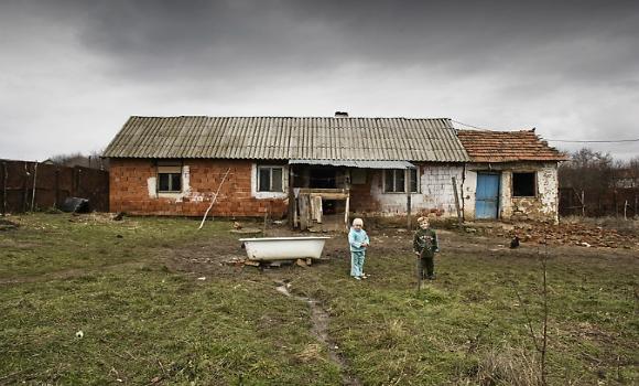 dvoje dece ispred zapuštene kuće na Kosovu