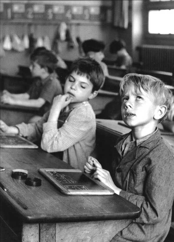 Crnobela fotografija dva dečaka sede u školskoj klupi