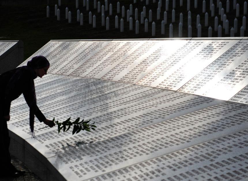 Žena polaže cvet na spomenik u Srebrenici