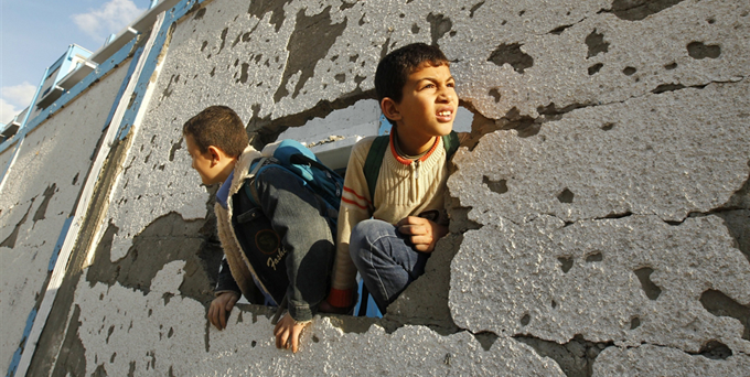 Palestinian schoolboys look through a hole at their damaged school in Gaza City on Saturday http://cnn.it/1k5mvkl