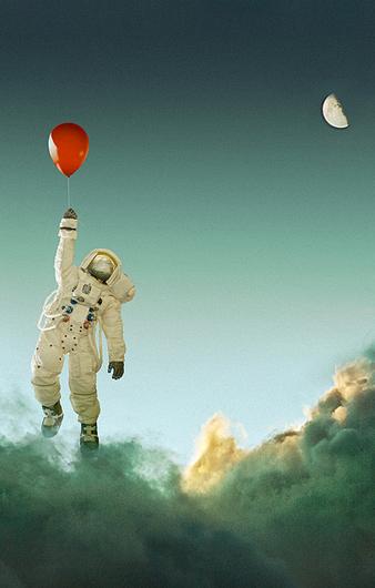 astronaut se drži za crveni balon