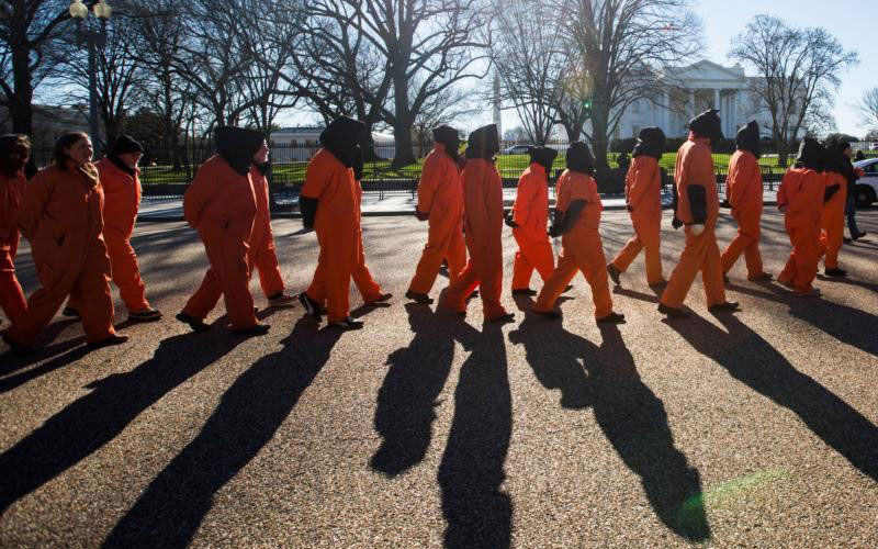 Activists dressed in orange jumpsuits representing detainees in the U.S.-run detention center at Guantanamo Bay, Cuba, protest in front of the White House (CNS)