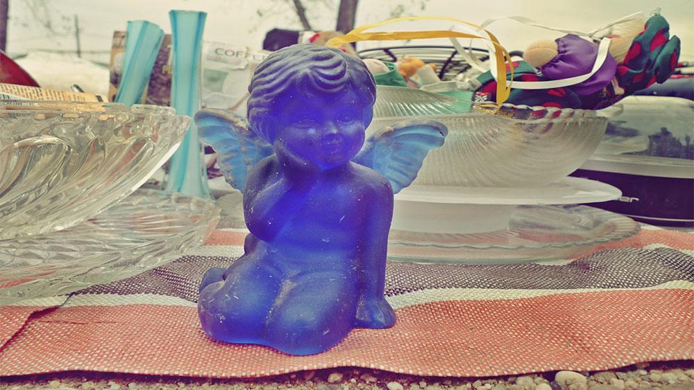 plava figurica anđela izložena na prodaju na buvljaku