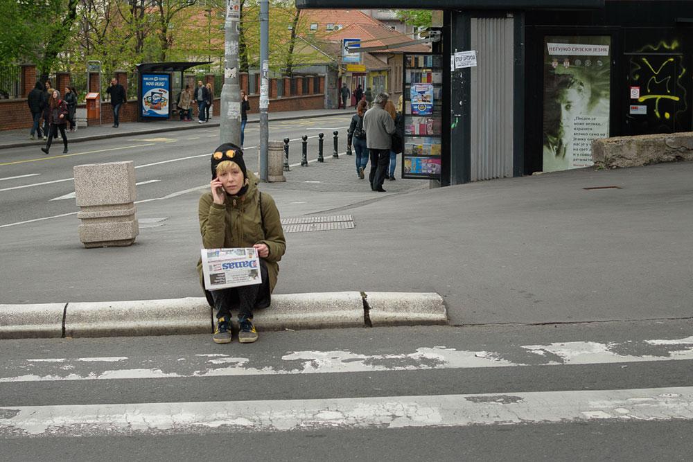 Devojka sedi na ulici