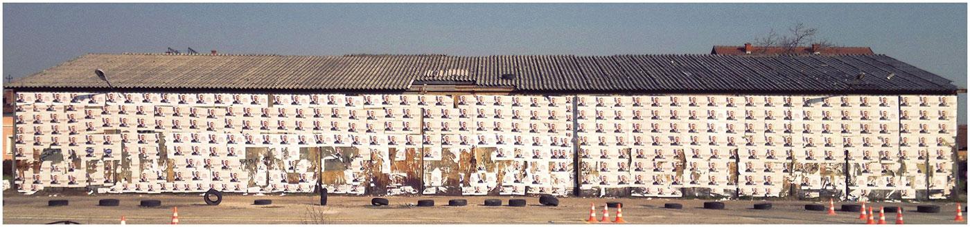 zgrada oblepljena plakatima sa Vučićevim likom