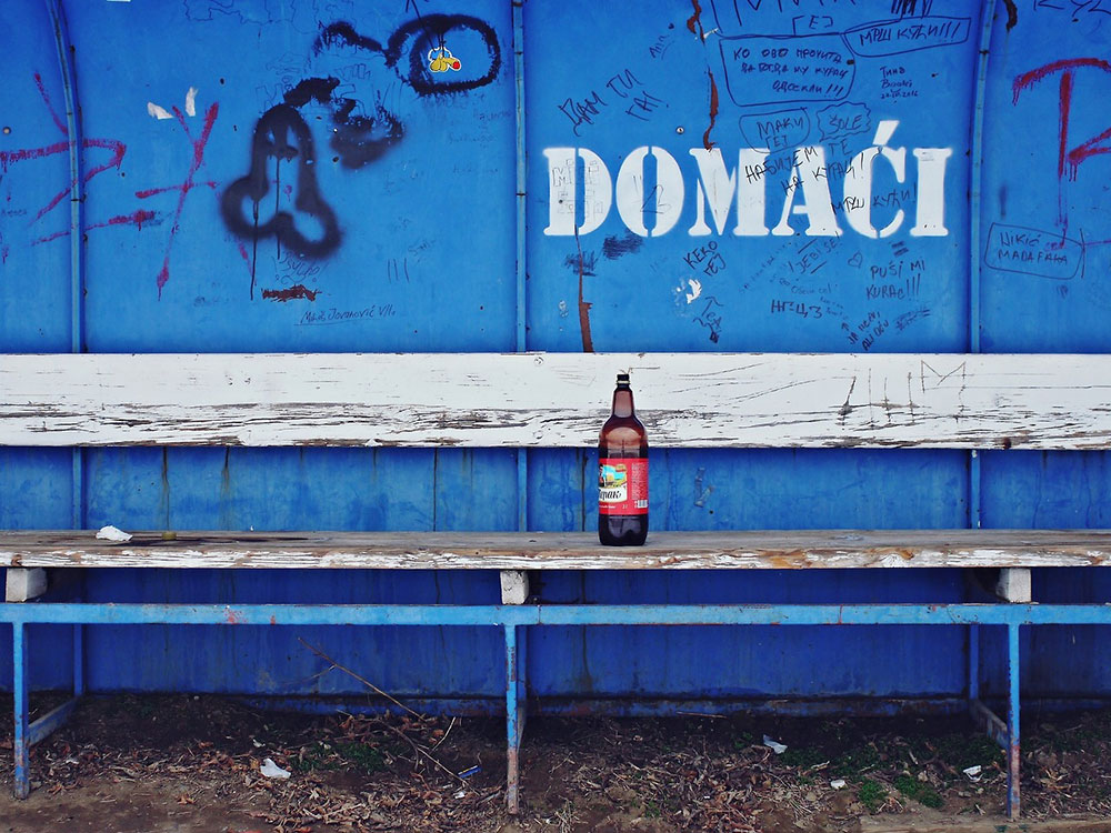 Flaša piva na klupi na fudbalskom terenu