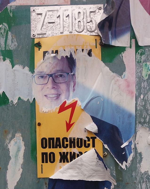 iscepan plakat sa likom Aleksandra Vučića ispod kojeg se vidi upozorenje: Opasnost po život