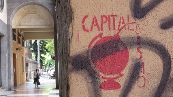 Crveni grafit na stubu u Bolonji: Capitalismo (sa globusom-bombom umesto tačke na 'i')