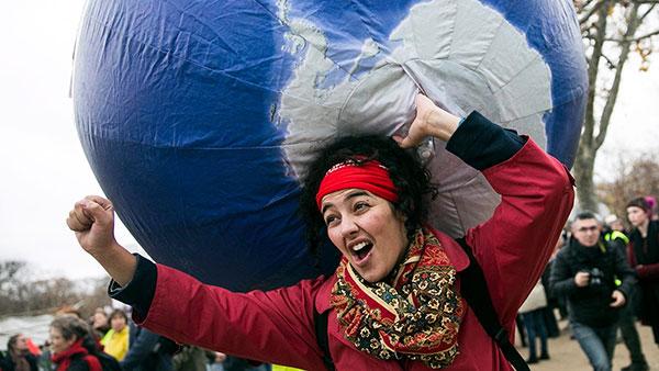 žena koja protestuje, u levoj ruci ima balon planetu Zemlju, desna ruka je stisnuta u pesnicu