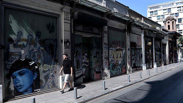 čovek prolazi pored zatvorenih radnji u Solunu