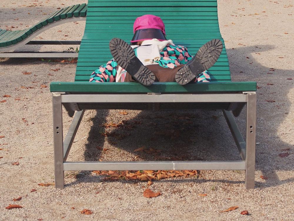 čovek spava na klupi u parku sa šeširom koji mu potpuno prekriva lice, slikano u Beču