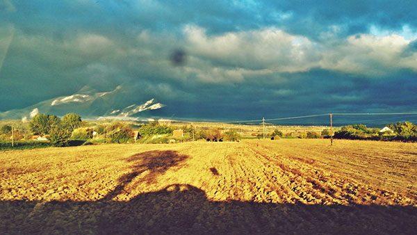 polja, kuće i oblačno nebo viđeni iz automobila u pokretu
