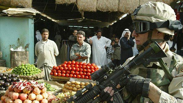 naoružani vojnik na pijaci među ljudima