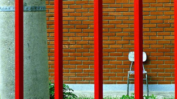drvena stolica iza rešetaka