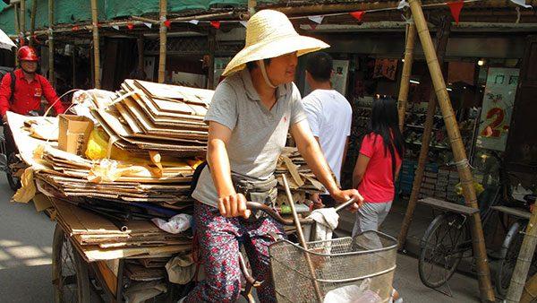 žena vozi bicikl sa prikolicom za sekundarne sirovine, Šangaj