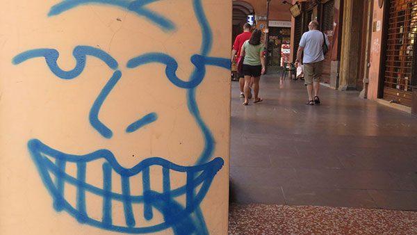 lice koje se smeje nacrtano na stubu u Bolonji