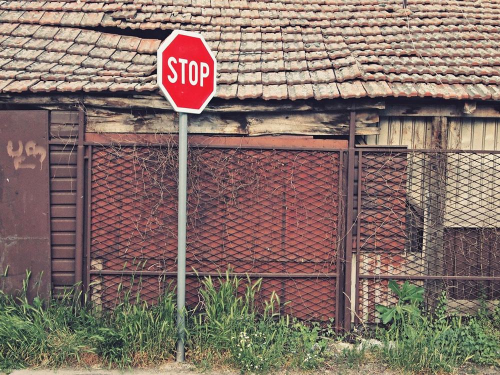 saobraćajni znak Stop ispred napuštene kuće