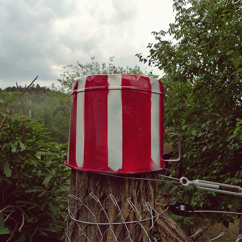 crveno-bela šerpa postavljena kao zabran na ogradu u polju