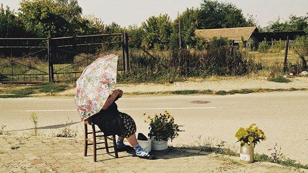 žena sa kišobranom prodaje cveće na ulici