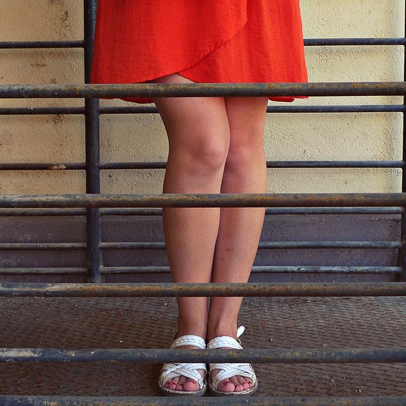 devojka u crvenoj suknji kojoj se vide samo noge