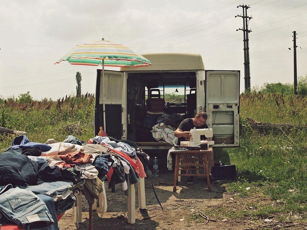 muškarac šije ispred kombija sa odećom