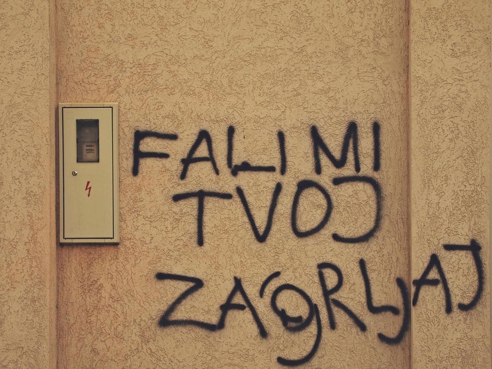 natpis na fasadi zgrade: Fali mi tvoj zagrljaj