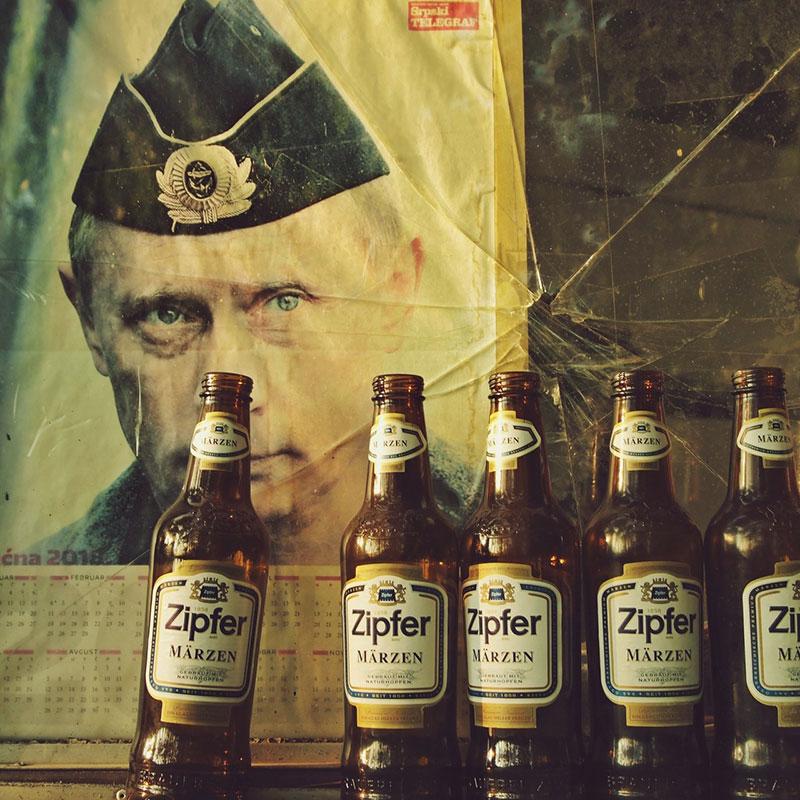 kalendar sa likom Putina ispred koga su prazne pivske flaše
