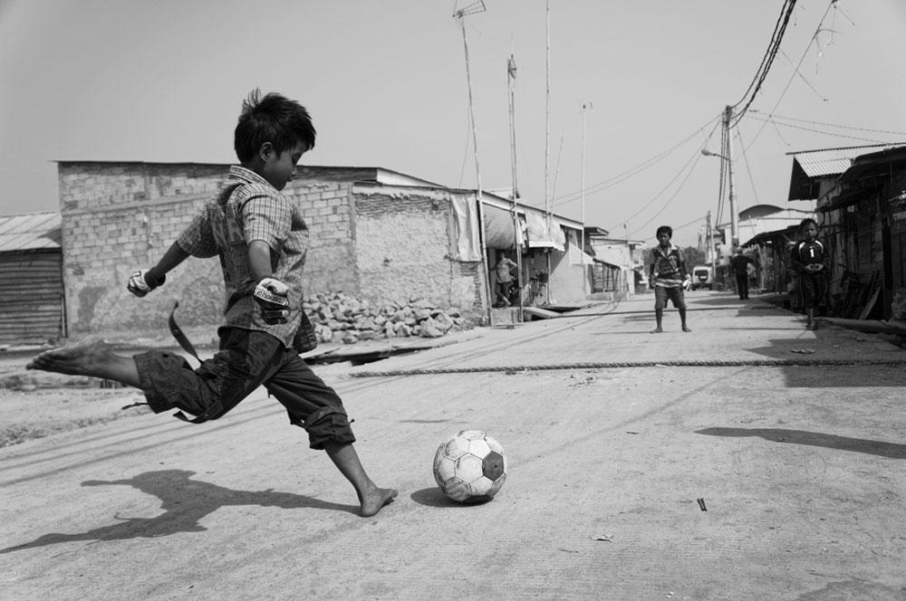 dečak šutira fudbalsku loptu na ulici