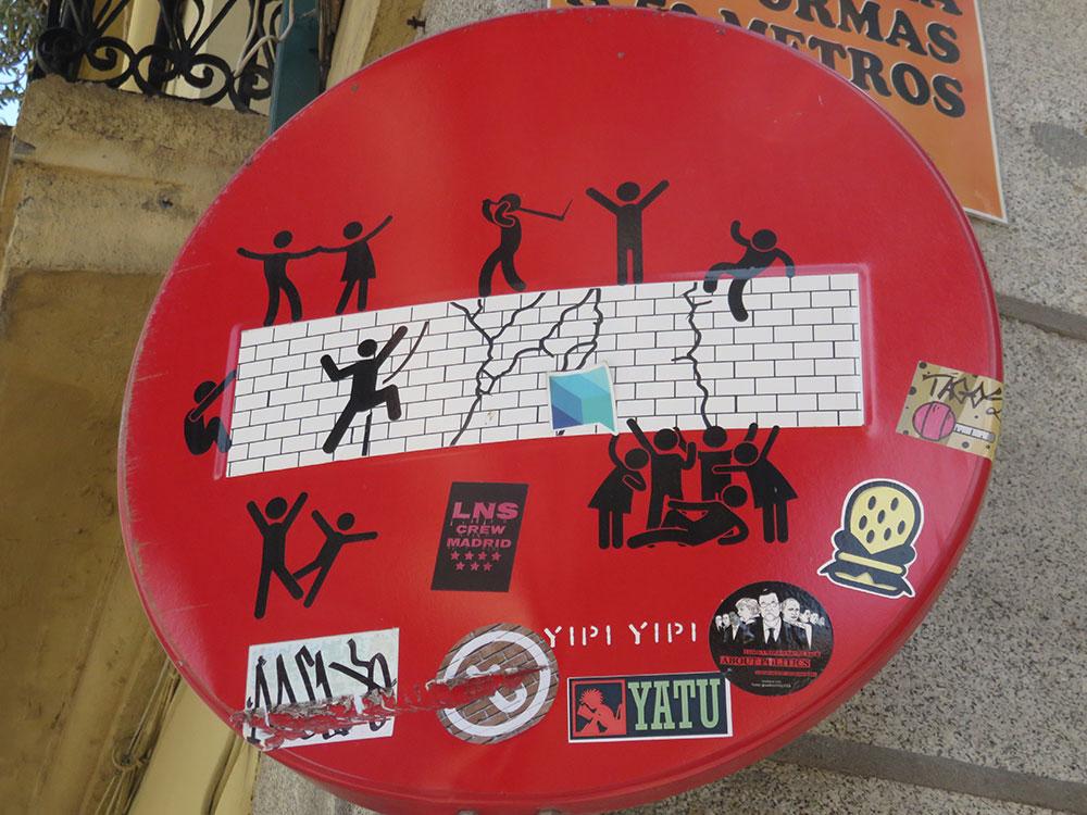 nacrtani čovečuljci na znaku za jednosmernu ulicu, koji preskaču i ruše znak zabrane