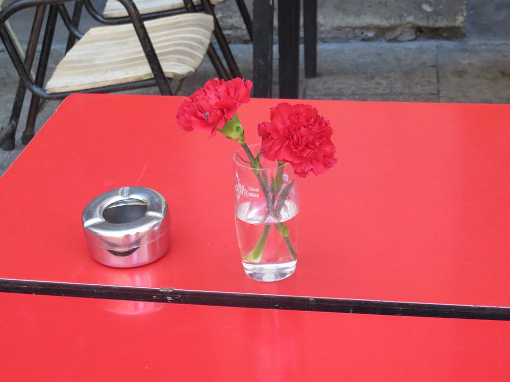 Crveni sto na kome su crveni kafanfili u čaši za vodu, Barselona