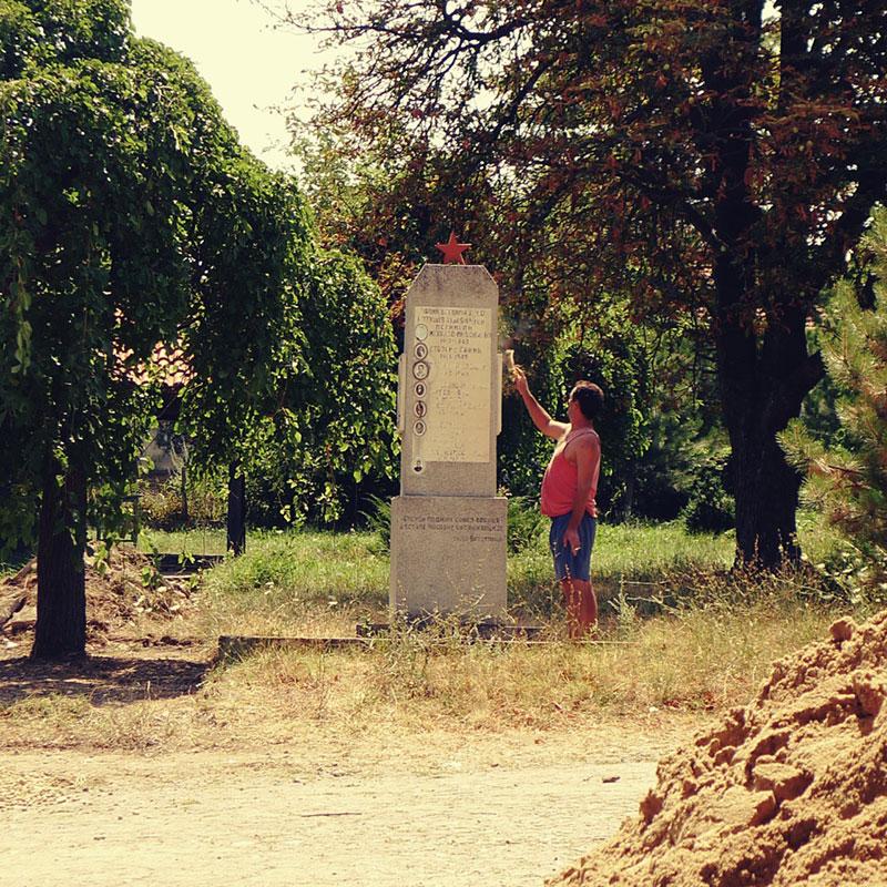 čovek ispred spomenika sa petokrakom