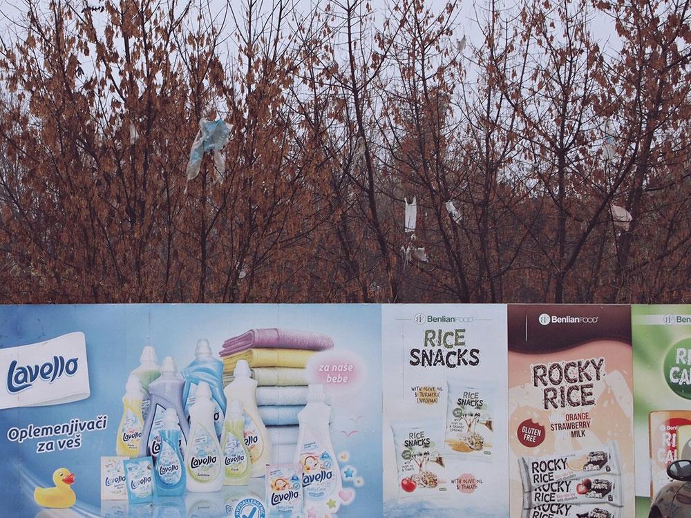 Ograda sa reklamama preko koje se vidi drveće na kojem su plastične kese