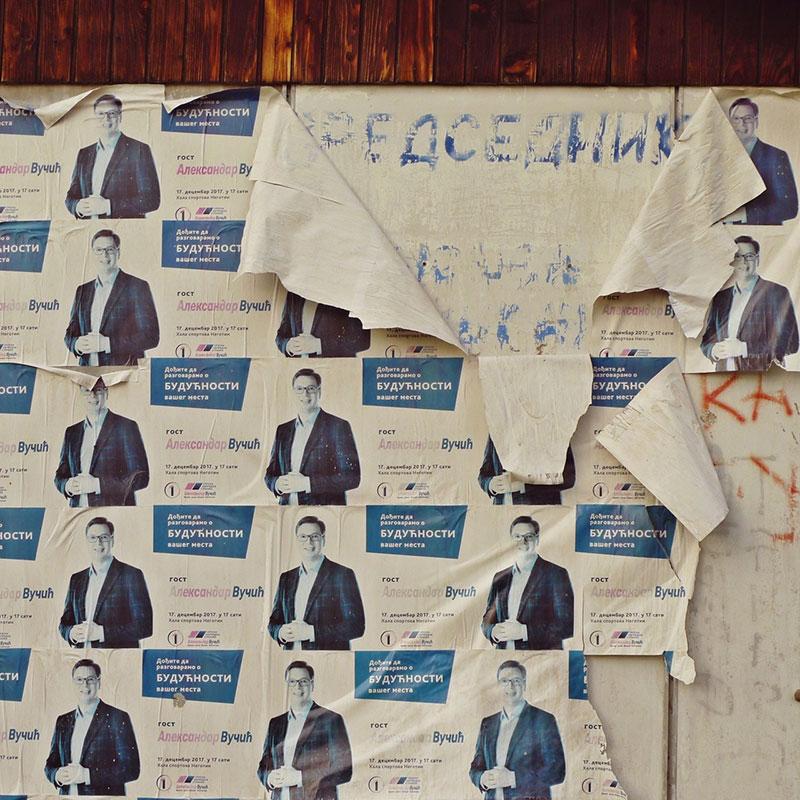 oglasna tabla na kojoj su izcepane plakate sa likom Vučića