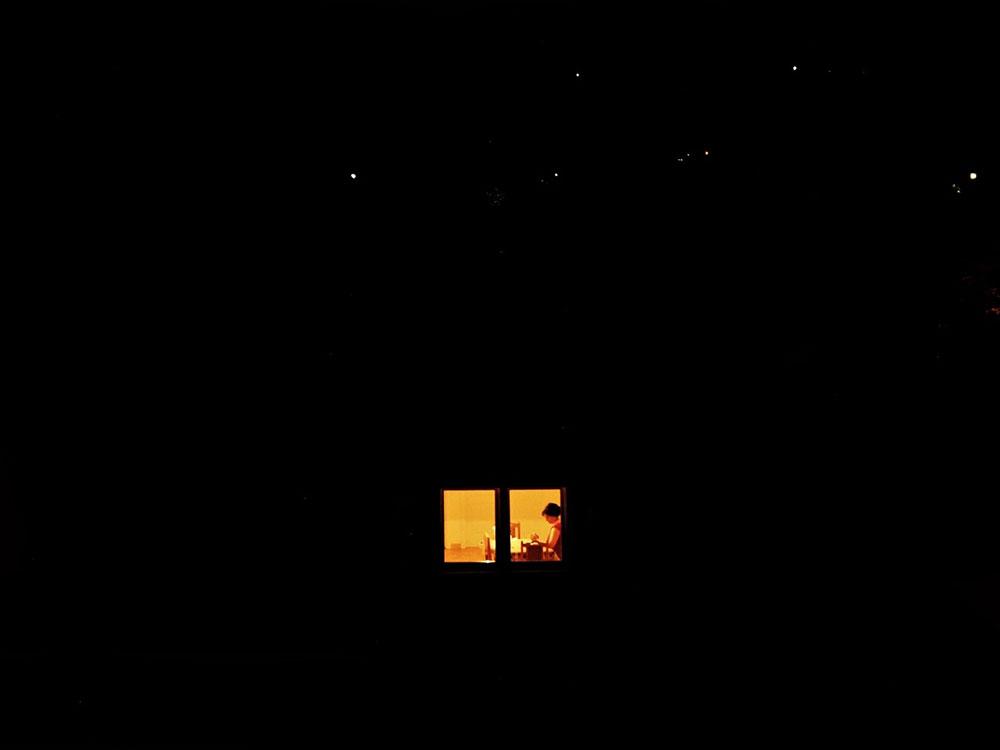 prozor kroz koji se vidi žena koja sedi
