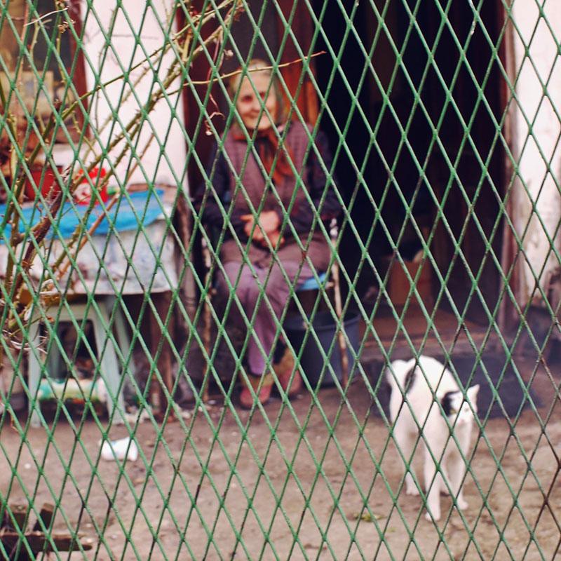 starica sedi ispred kuće
