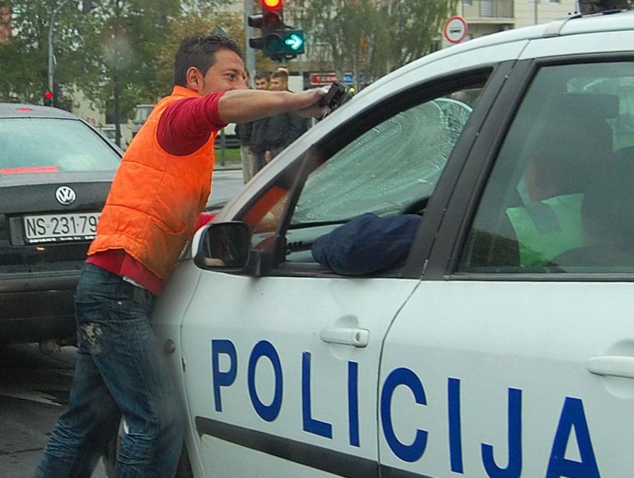 Čovek pere šoferšajbnu na policijskim kolima