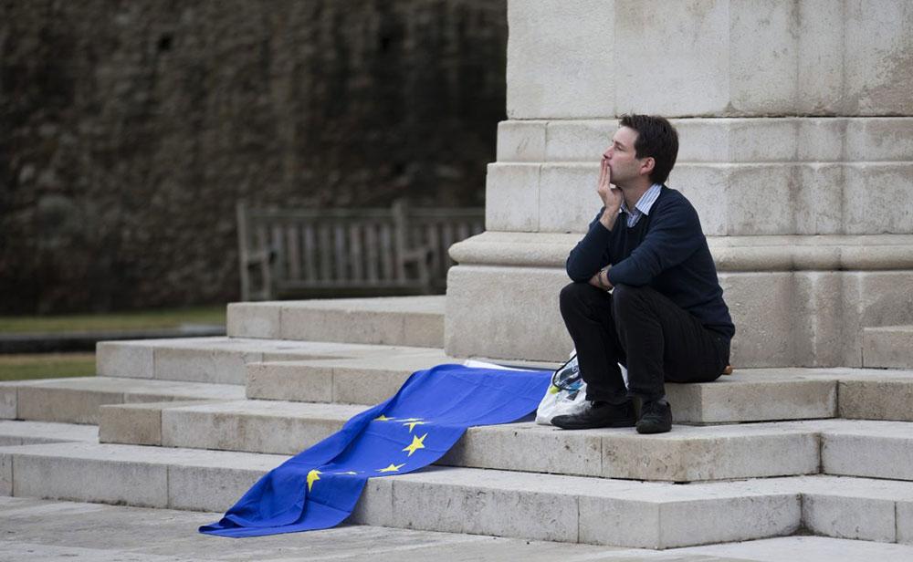 Čovek sedi na stepeništu sa zastavom EU