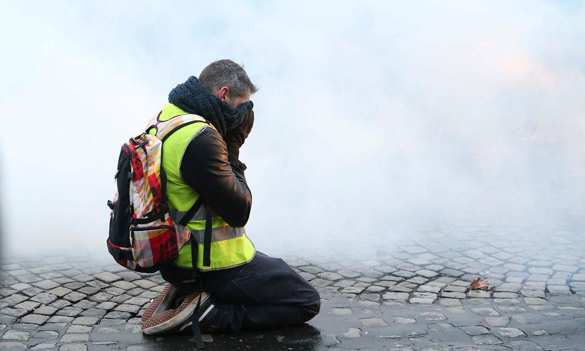 Protestant na ulici u oblaku suzavca, Pariz