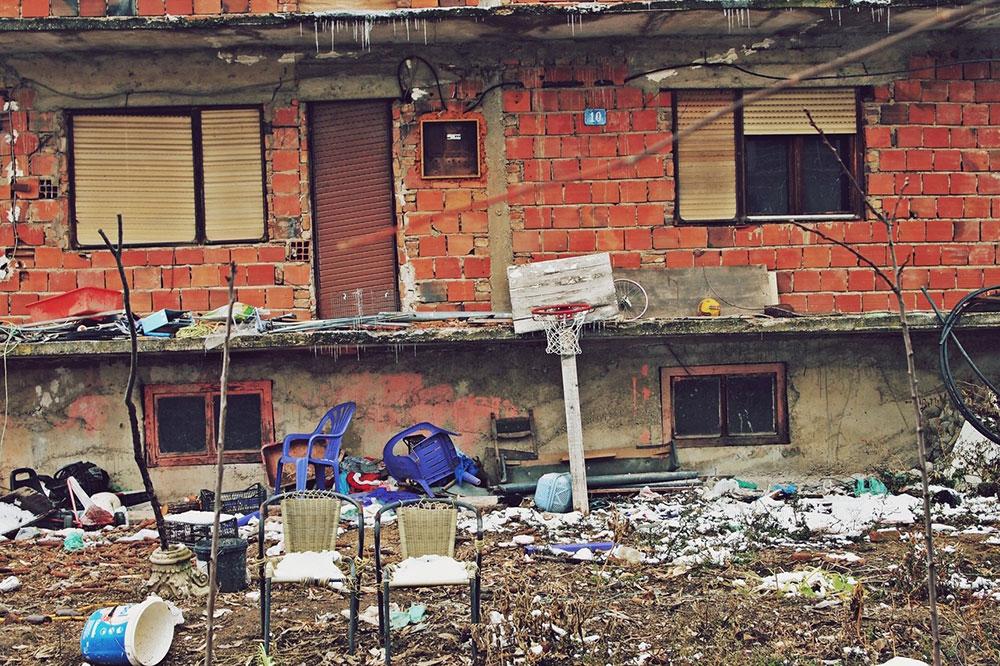 dvorište nezavršene kuće po kojem su razbacane stvari i smeće