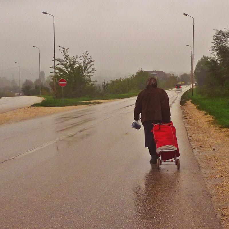 Žena vuče torbu i hoda kolovozom