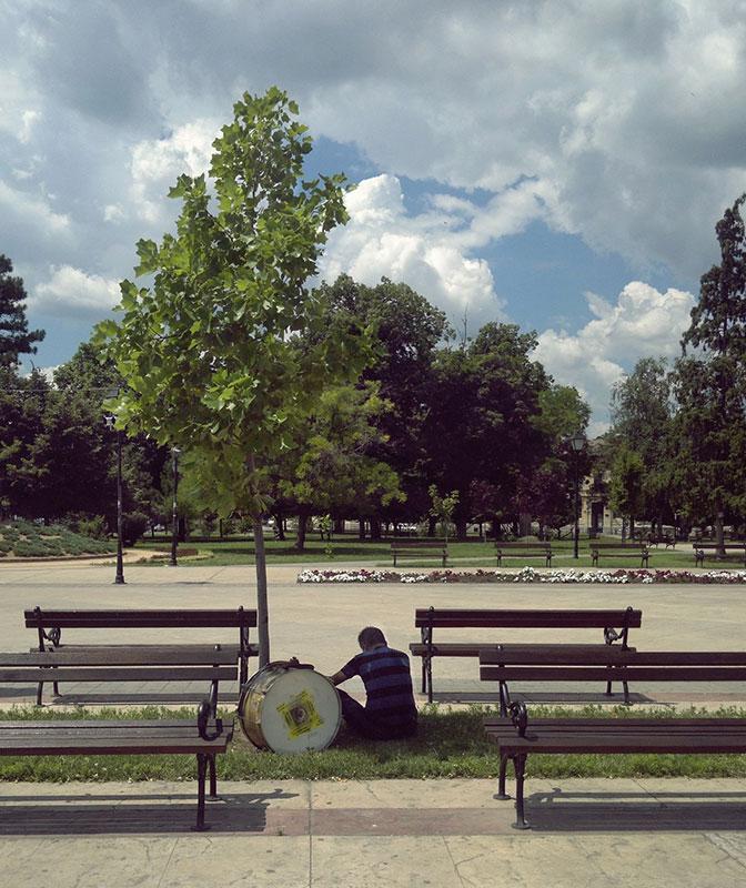 Čovek sa dobošem sedi u parku na travi