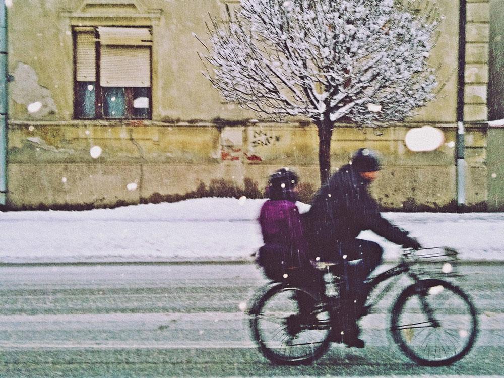 dvoje na biciklu, sneg pada