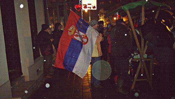ljudi na ulici sa zastavom Srbije