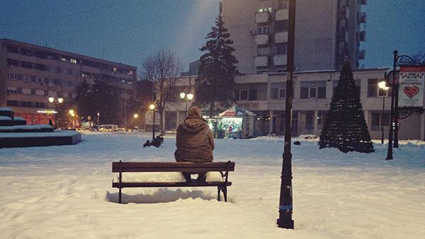 čovek sedi na klupi u parku