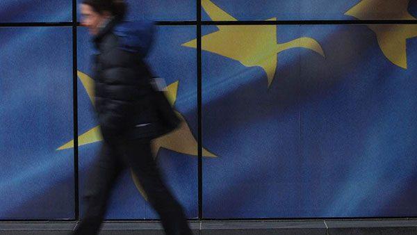 Žena prolazi pored zastave EU